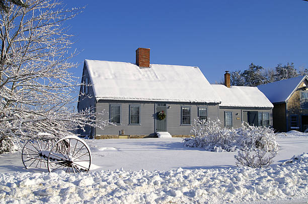 House covered in snow with two chimneys and many windows stock photo