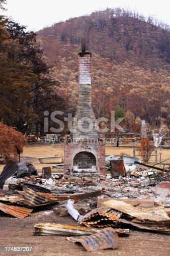 The remains of a house destroyed by a catastrophic bushfire.  The chimney stands stark against the backdrop of a charred hillside. In the foreground is a jumble of burnt and twisted roofing iron.