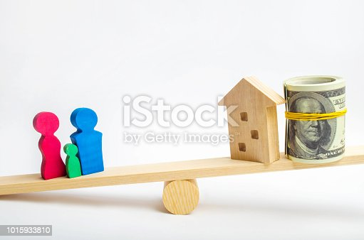 istock house, dollars and family on the scales. balance. buying, selling, renting a house and an apartment. credit. mortgage. property. investment in real estate. saving money. Home loan 1015933810