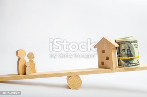 istock house, dollars and family on the scales. balance. buying, selling, renting a house and an apartment. credit. mortgage. property. investment in real estate. saving money. Home loan 1015933822