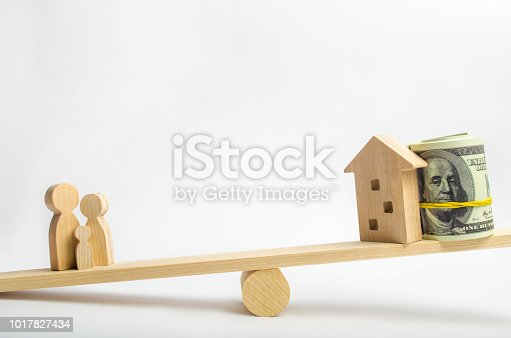istock house, dollars and family on the scales. balance. buying, selling, renting a house and an apartment. credit. mortgage. property. investment in real estate. saving money. Home loan 1017827434