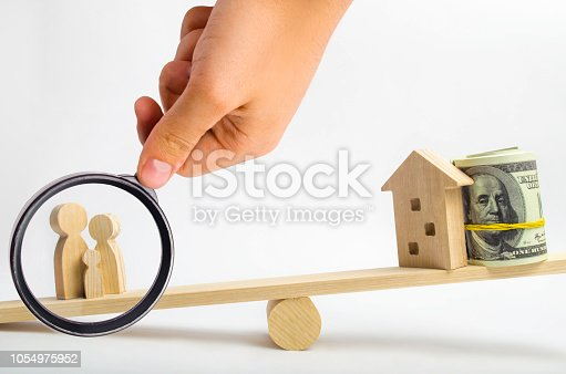 istock house, dollars and family on the scales. balance. buying, selling, renting a house and an apartment. credit. mortgage. property. investment in real estate. saving money. Home loan 1054975952