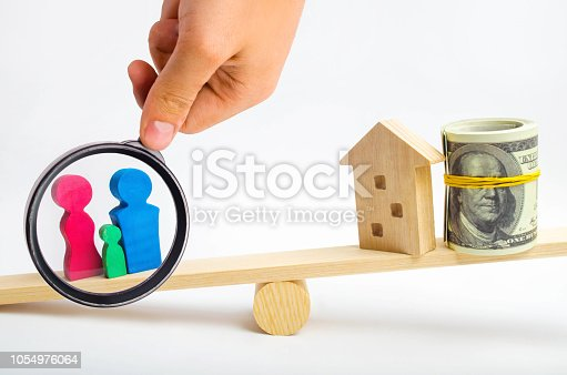 istock house, dollars and family on the scales. balance. buying, selling, renting a house and an apartment. credit. mortgage. property. investment in real estate. saving money. Home loan 1054976064