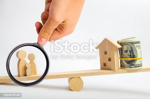 istock house, dollars and family on the scales. balance. buying, selling, renting a house and an apartment. credit. mortgage. property. investment in real estate. saving money. Home loan 1054976162