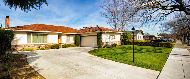 Panoramic view of a house, empty driveway and sidewalk in San Jose California on a sunny day