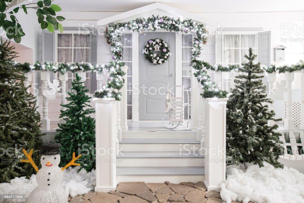 Hauseingang eingerichtet für einen Urlaub. Weihnachts-Dekoration. Girlande aus Tannenzweigen Baum und Lichter auf dem Geländer – Foto