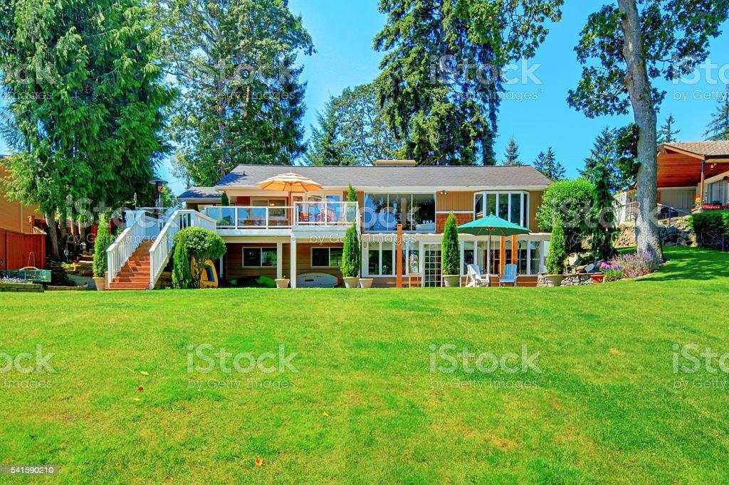 House exterior with impressive backyard landscape design and patio area. stock photo