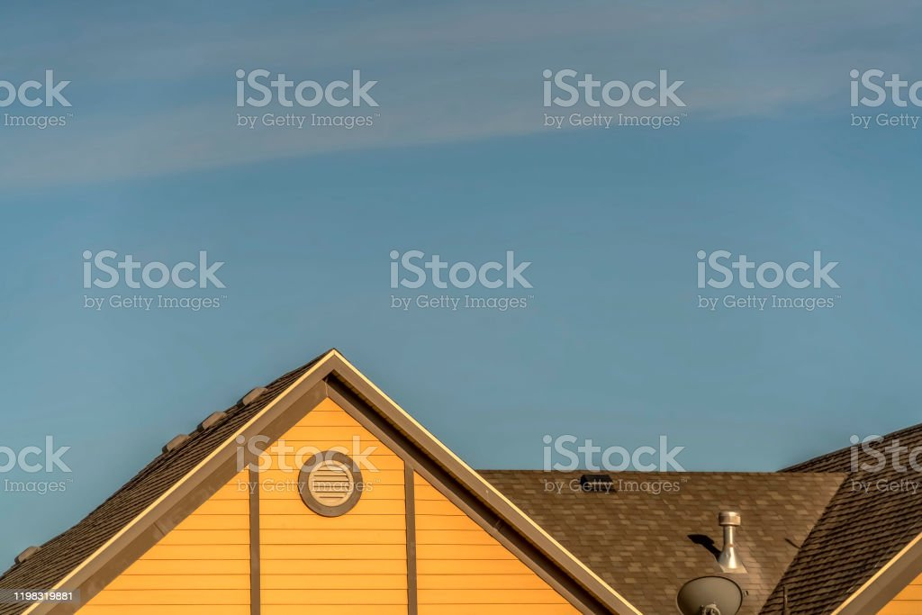 house exterior with roof shingles and round gable window against blue picture id1198319881