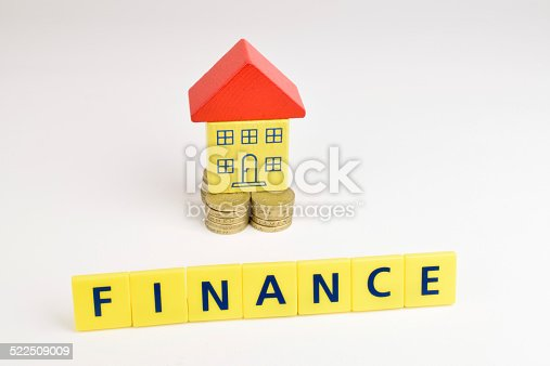 A toy house sitting on a stack of coins with the words, 'Finance'  in front of it.