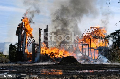 Old farm house completely consumed by fire is burnt to the ground.