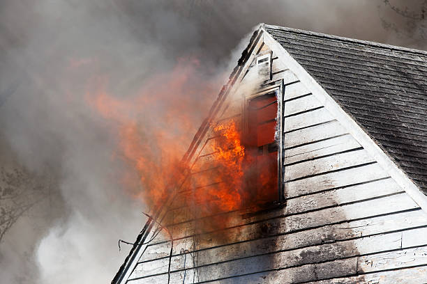 House Fire with Flames through Attic Window stock photo