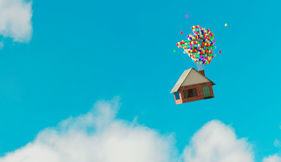 Small house flys up in the air after balloons with helium has been attaches to the chimney.