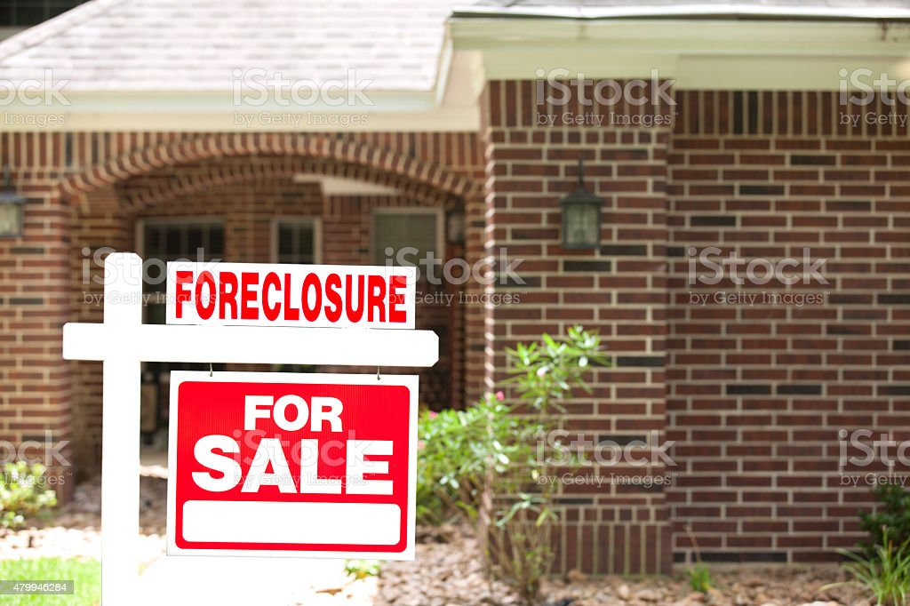 House for sale, foreclosure sign in front yard. No people. stock photo