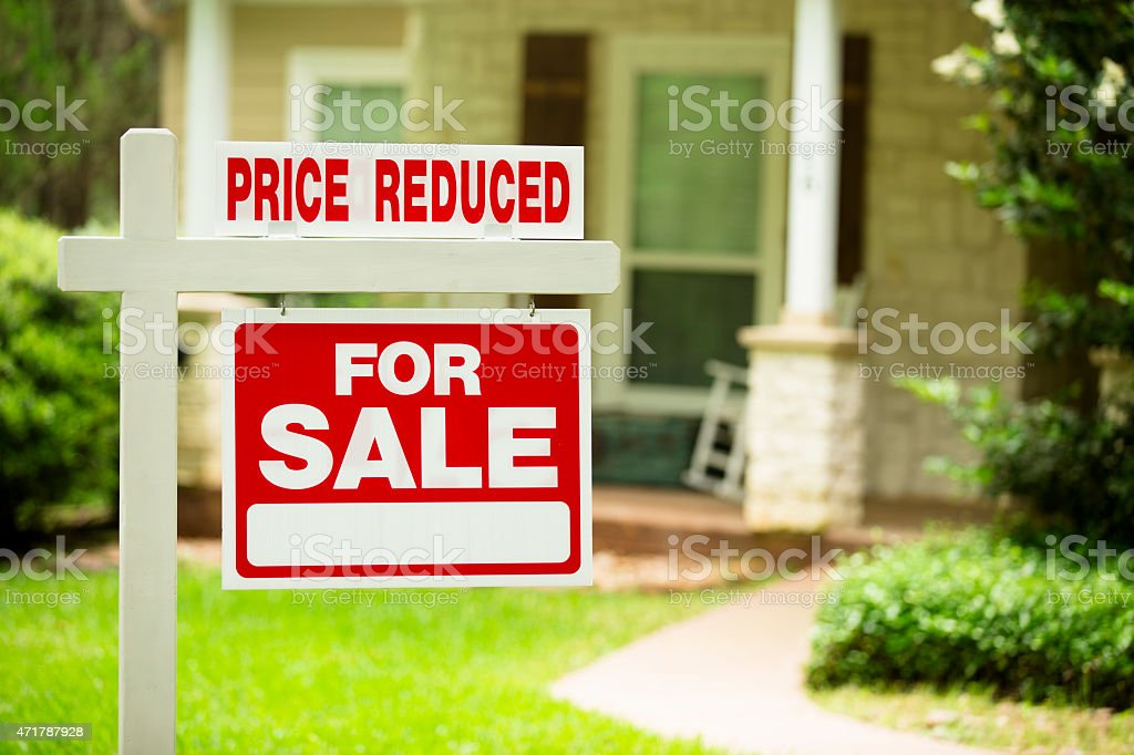 House for sale, price reduced. Real estate sign. Front yard. stock photo