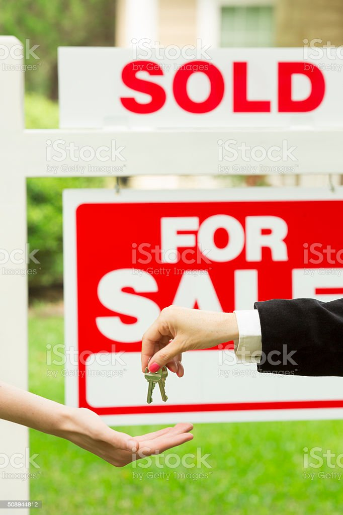 Close-up of real estate agent giving house keys to new buyer in front...