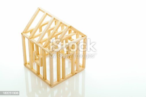 A small wooden house frame on white with reflection.