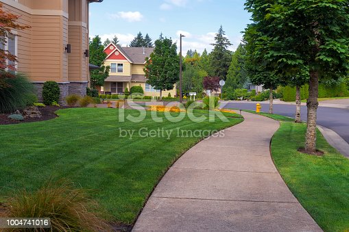 House frontyard and parking strip freshly mowed green grass lawn in North American suburban residential neighborhood
