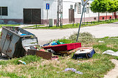 istock House furniture dumped in the garbage on the street in the city near metal dumpster junk can 993645130