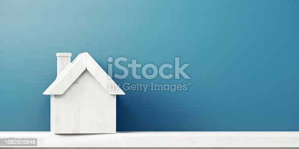 House icon is standing in front of blue wall. Horizontal composition with copy space, Great use for real estate concepts.