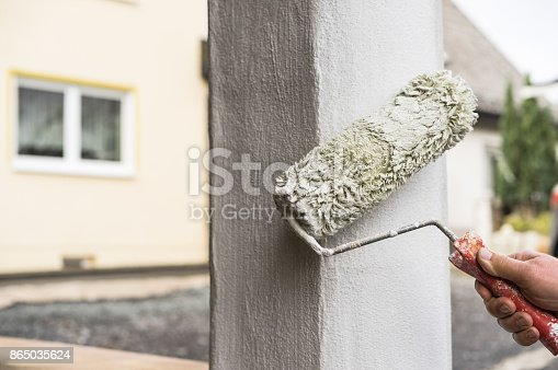 835790922 istock photo House improvement professional painter is painting column with paint roller exterior 865035624