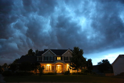 A well appointed house is lit up while a large thunderstorm moves in overhead. Ample copy space above.