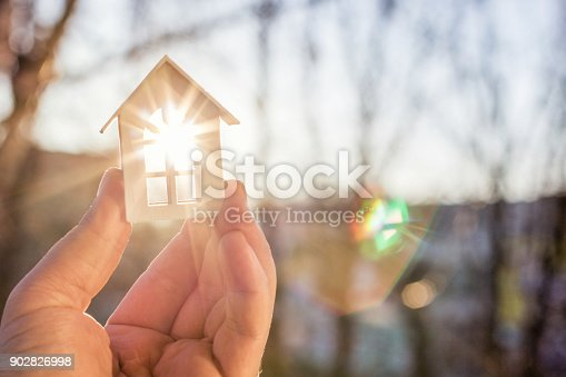 istock House in hand in the rays of the sun. 902826998