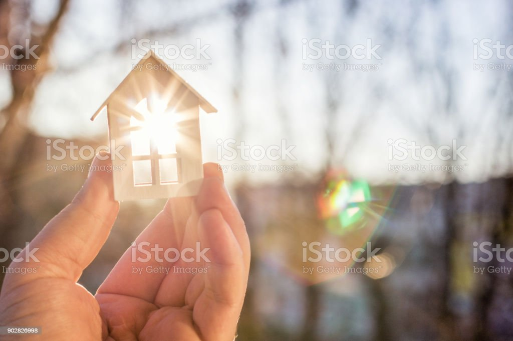 House in hand in the rays of the sun. stock photo