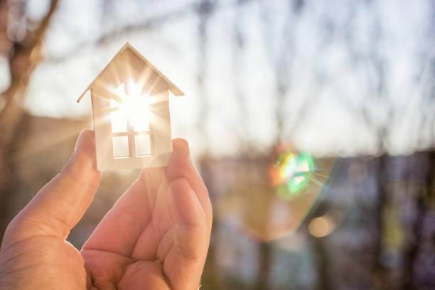 huis in hand in de stralen van de zon. - hand constructing industry stockfoto's en -beelden
