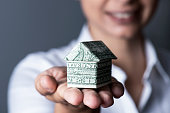 Caucasian young businesswoman is holding a origami house made of a1 dolar bill, horizontal