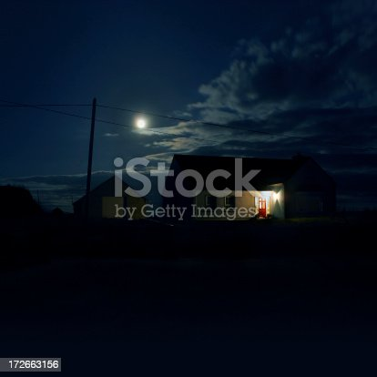 House in the night lit by the moon