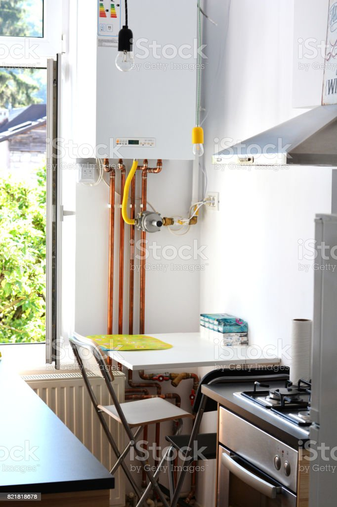 House interior – gas boiler with copper pipes in kitchen stock photo