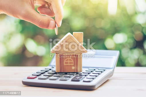 istock House is placed on the calculator. hand that is coin down the house. planning savings money of coins to buy a home concept for property, 1171493612