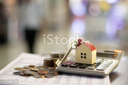 istock House is placed on the calculator. Imagine calculating to buy a home. planning savings money of coins to buy a home concept for property, mortgage and real estate investment.to buy a house. 1174390766