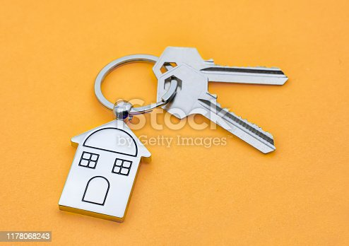 istock House Key And Key chain On orange background 1178068243