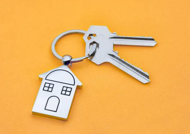 House Key And Key chain On orange background stock photo