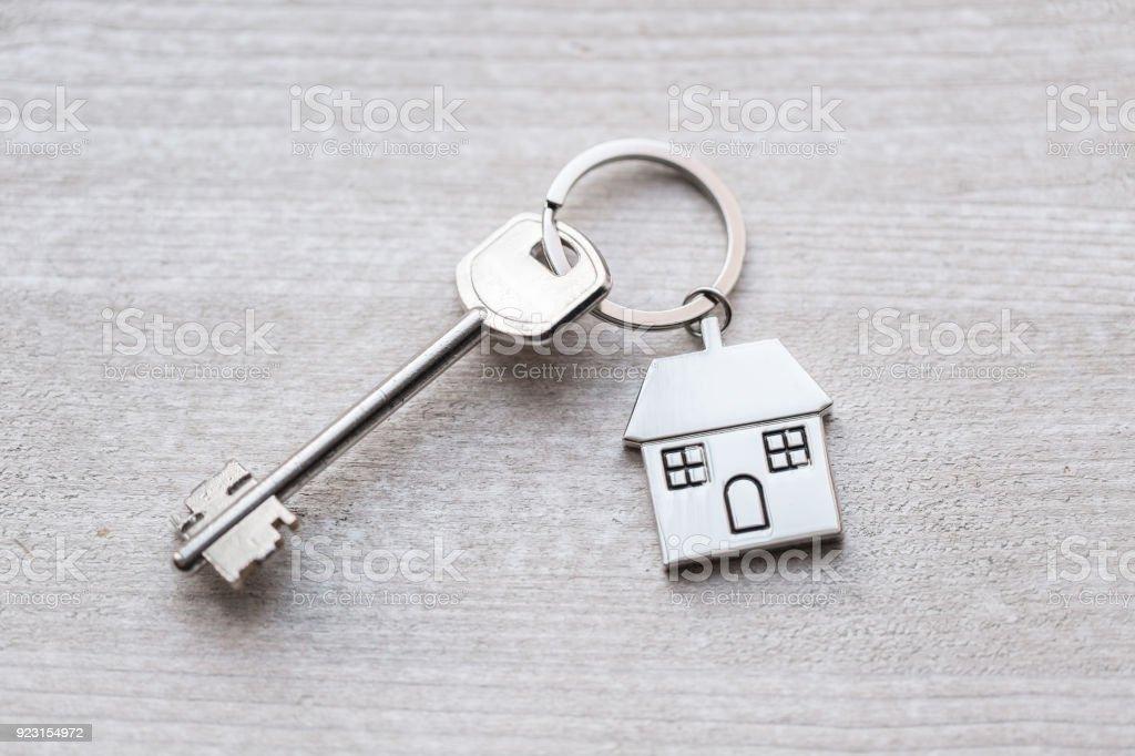 Llave de la casa y llavero en forma de casas se encuentra en tablas de madera. Concepto de bienes raíces, hipotecas, mudanza o alquiler de propiedad. - foto de stock