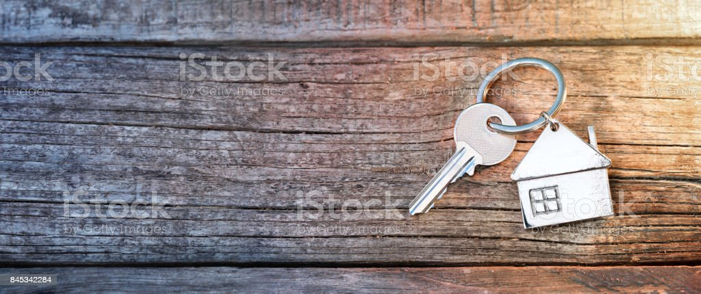 House Key And Keychain On Wooden Table stock photo