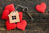 ミニハート、コピースペースで飾られた木製の背景にホームキーリングとハート形の家の鍵