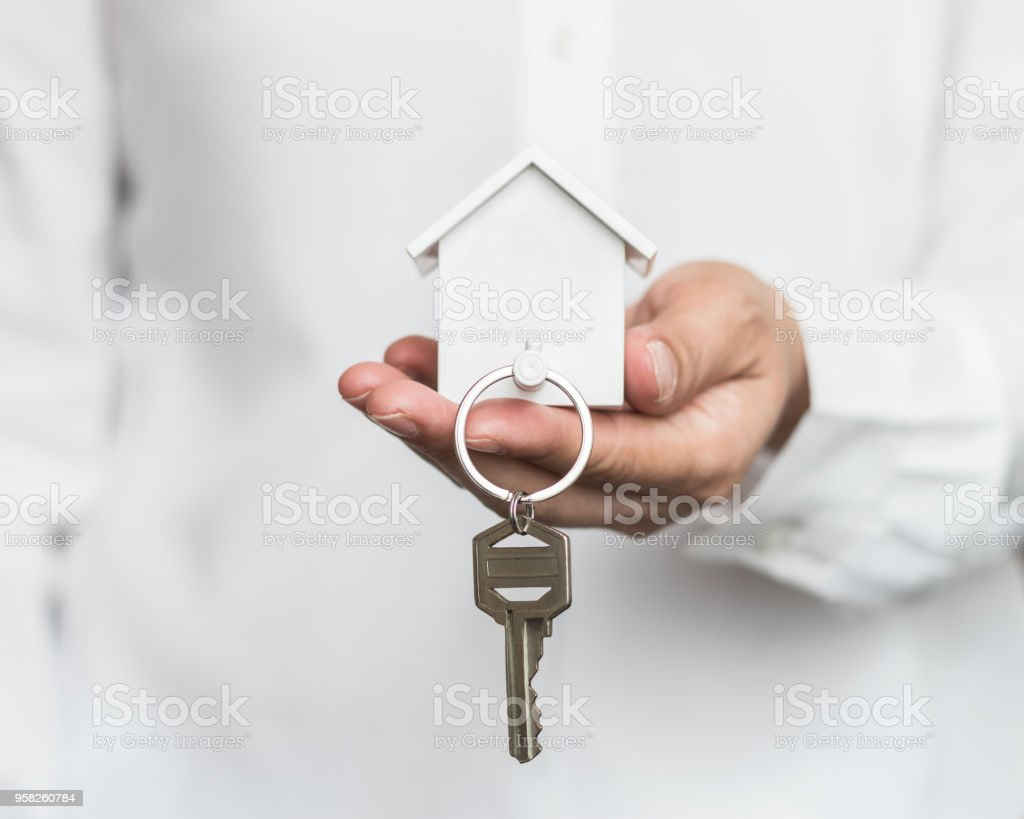 House key in home insurance broker agent's hand protection or in salesman person giving to buyer customer stock photo