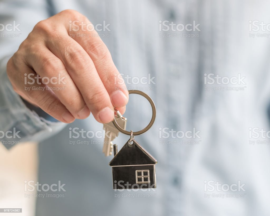 House key in real estate sale person, landlord or home Insurance broker agent's hand giving to buyer customer for new family property assurance concept stock photo