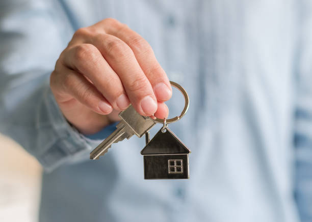 House key in real estate sale person or home Insurance broker agent's hand giving to buyer customer stock photo