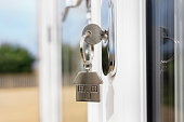 istock House key on a house shaped silver key ring in the lock of a door 1219401766