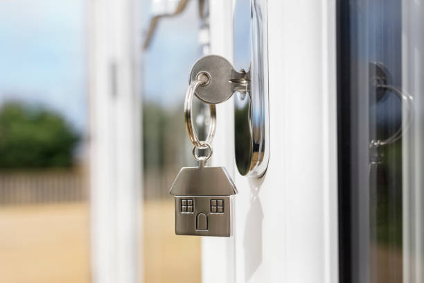 House key on a house shaped silver key ring in the lock of a door stock photo