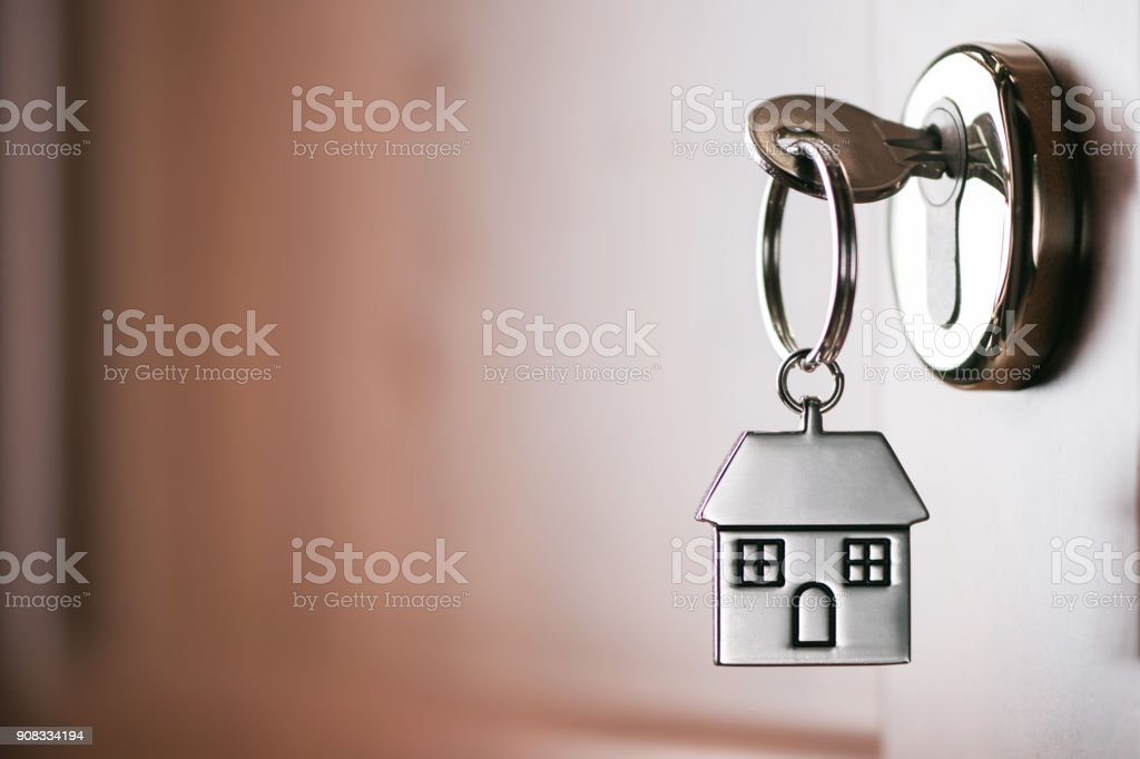 House key on a house shaped silver keyring in the lock of a entrance  brown door stock photo