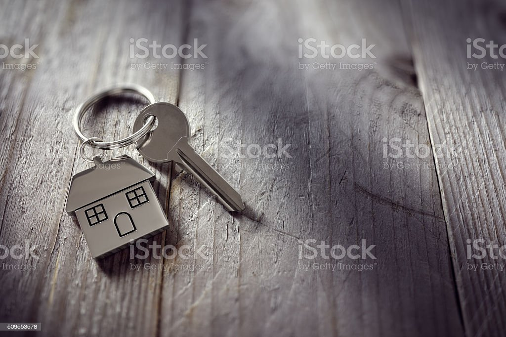 House key on a house shaped keychain resting on wooden floorboards...