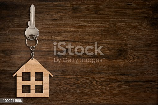 istock House key on keychain - wood background 1000911898