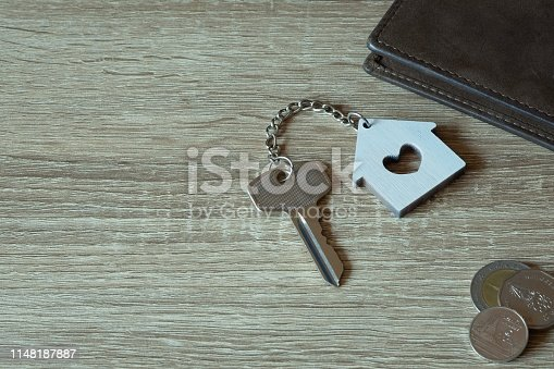 1135927471 istock photo House key with home keyring and wallet on wood table, copy space 1148187887