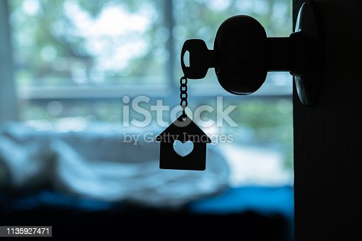 House key with home keyring in keyhole on wood door, copy space