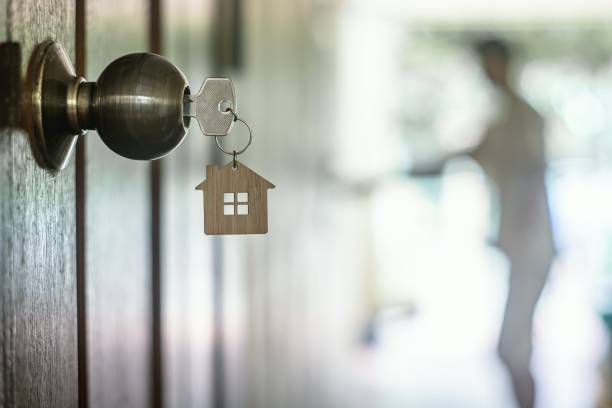 chave da casa com o chaveiro home no buraco da fechadura na porta de madeira, espaço da cópia - chave - fotografias e filmes do acervo