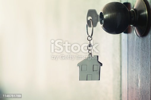 1135927471 istock photo House key with home keyring in keyhole on wood door, copy space 1145751759